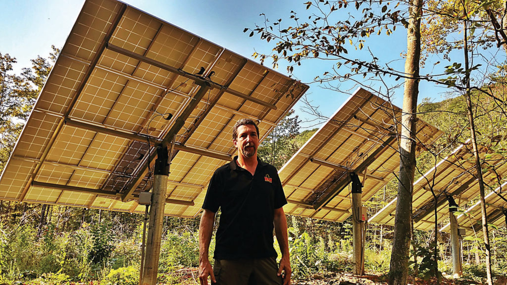 Bill Laberge standing with the solar panels at Emerald Lake Park